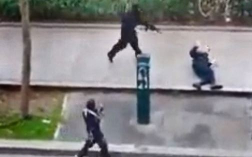 In this photo, captured from a video, gunmen are seen pointing their guns at a police officer outside the Charlie Hebdo office in Paris. He was later shot in the head.